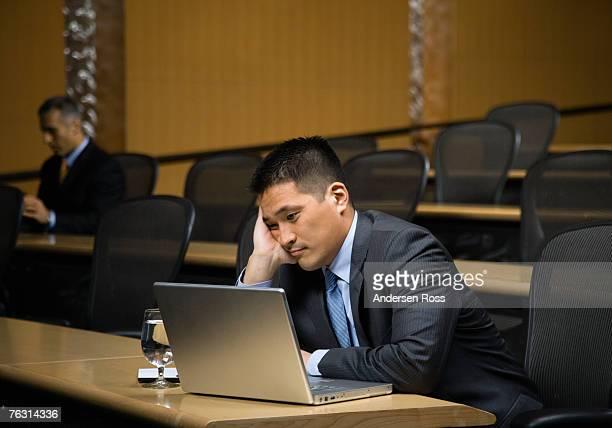 Business man using laptop in auditorium