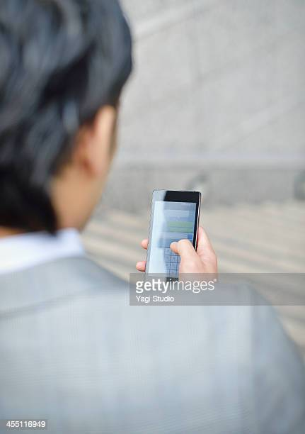 Business man using smartphone in buildings