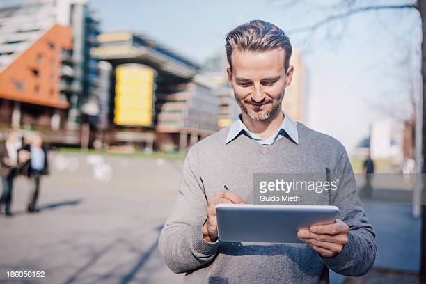 Business man using tablet pc in urban scene