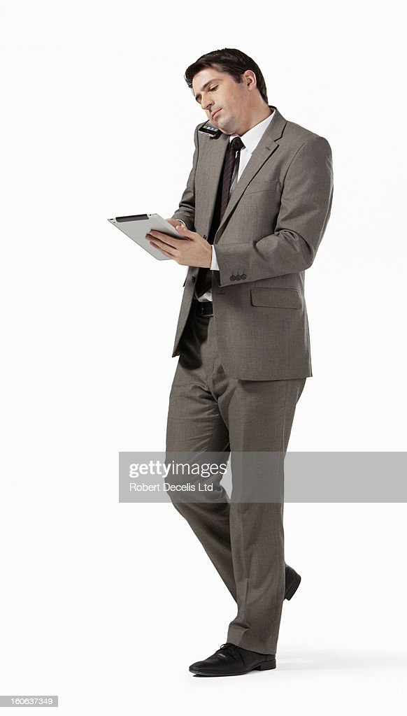 Business man using tablet whilst using smart phone : Stock Photo