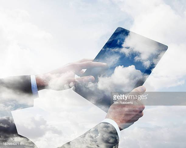 Business man using tablet with clouds.