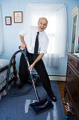 Business man vacuuming bedroom carpet, with antique furniture in room.