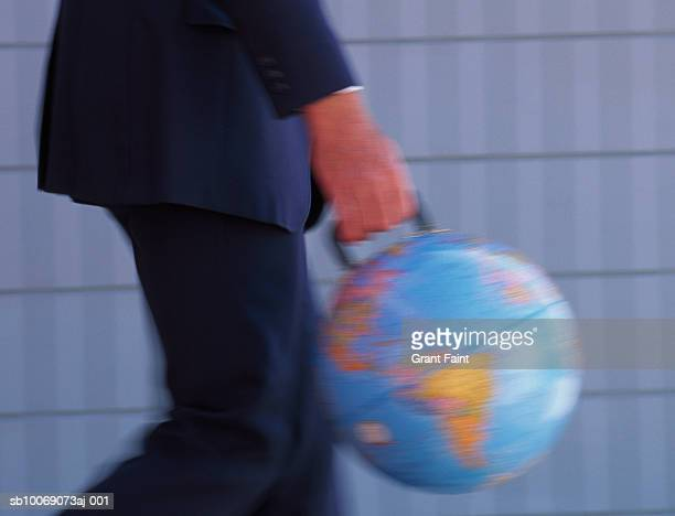 Business man walking, carrying globe with handle, mid section