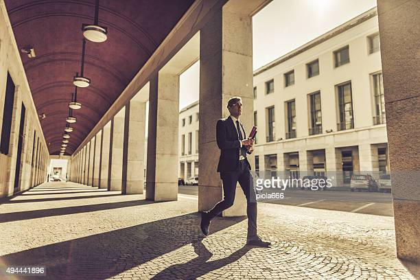 Business man walking in a colonnade