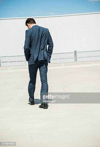 Business man walking on parking level, back view