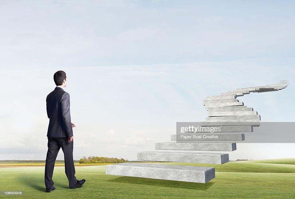 Business man walking toward floating stairs : Stock Photo