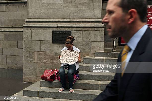 A business man walks by a homeless woman holding a card requesting money on September 28 2010 in New York City A new report released by the US Census...