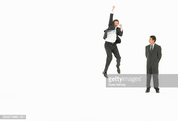 Business man watching colleague jumping