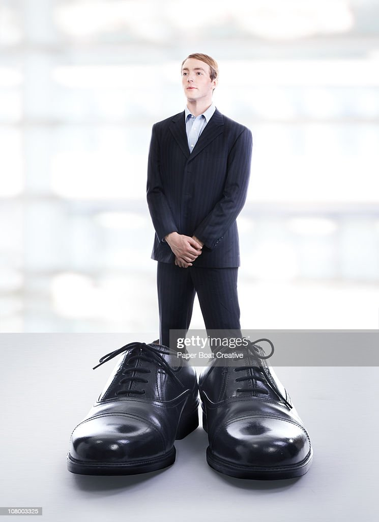 business man wearing extremely large black shoes