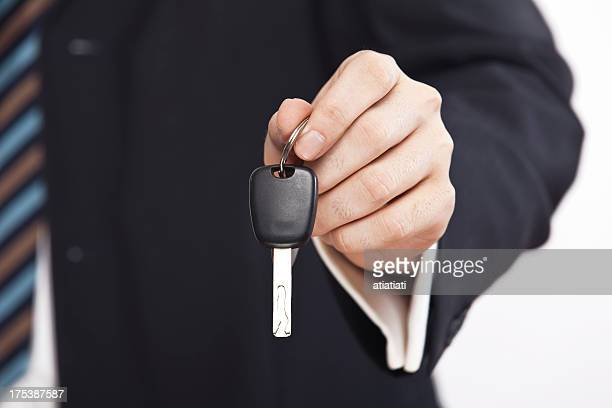 Business man with a striped tie holding a car key