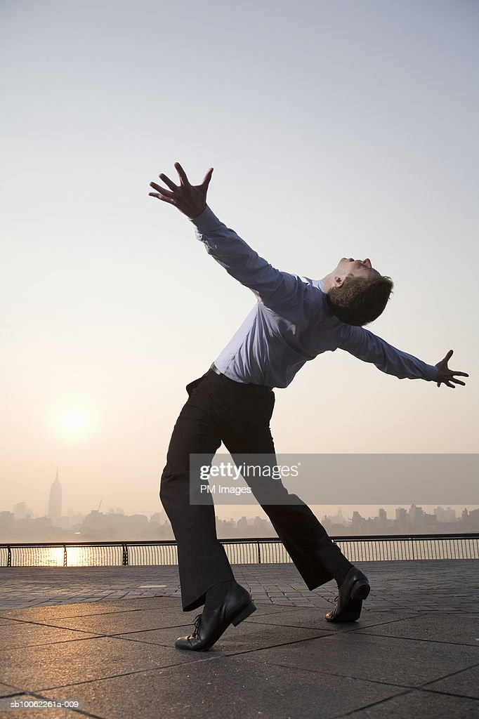 Business man with arms outstretched, New York City in background : Stock Photo
