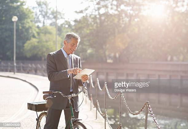 Business man with bike using digital tablet.