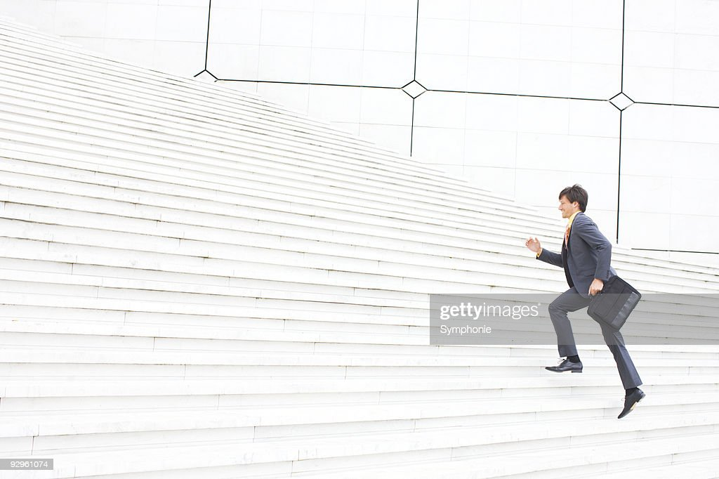 Business man with brief case running up steps : Stock Photo