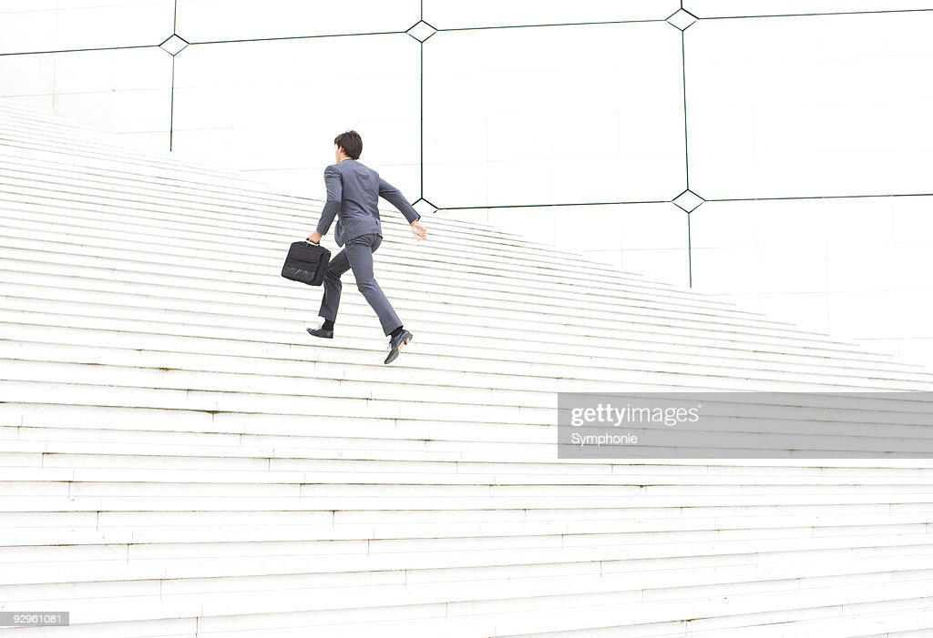 Business man with briefcase running up steps  : Stock Photo