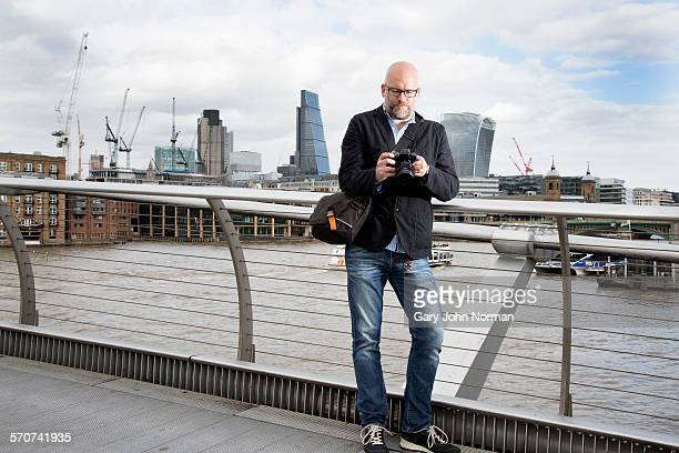 Business man with camera on Millenium Bridge.