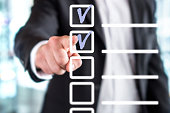 Business man with checklist and to do list. Man writing and drawing v sign check marks with hand and finger in square box. Project management, planning and keeping score of completed tasks concept.
