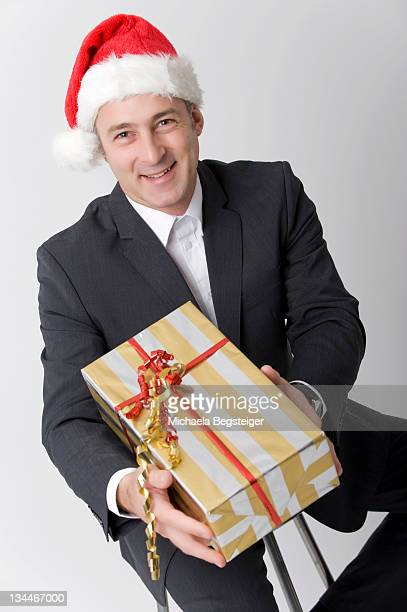 Business man, with Christmas present and Santa hat
