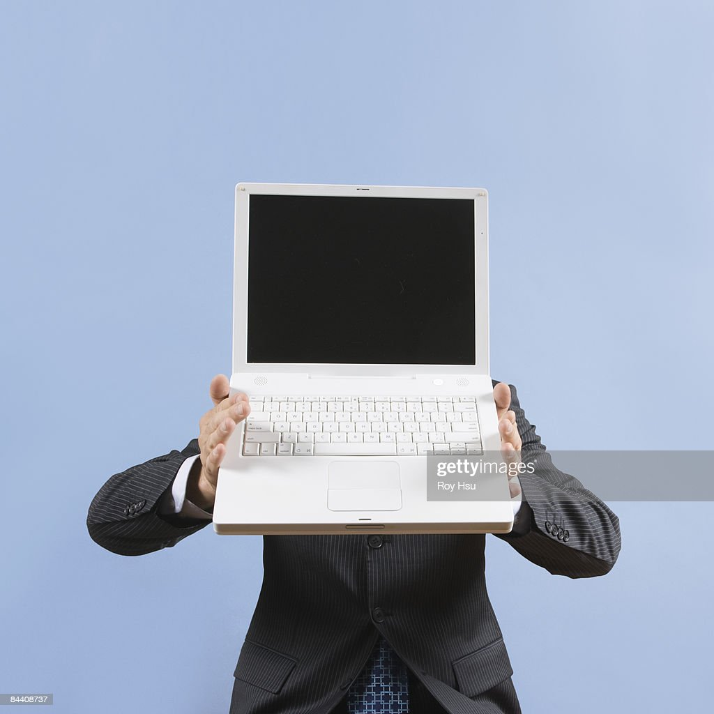 Business man with computer in front of face : Stock Photo