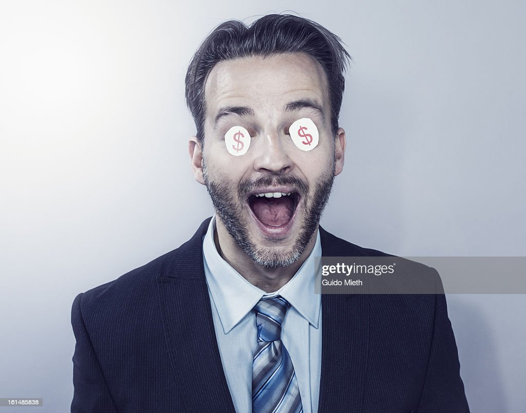 Business man with dollar signs in his eyes. : Stock Photo