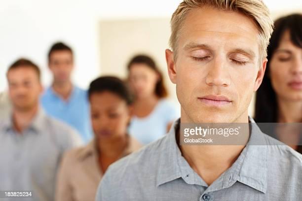 Un hombre de negocios con los ojos cerrados y colegas en el fondo