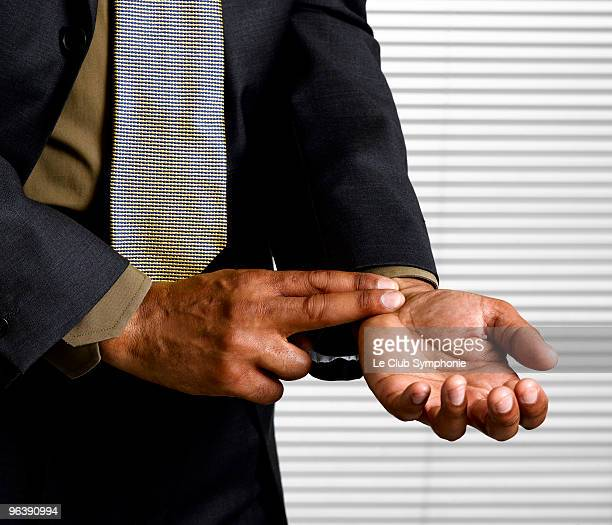 Business man with finger on pulse