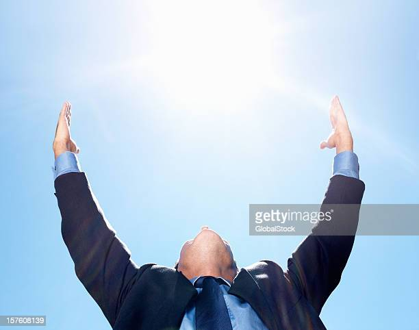Business man with hands raised against blue sky
