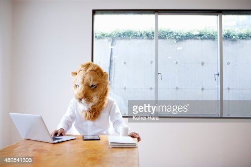 A business man with lion head working at office