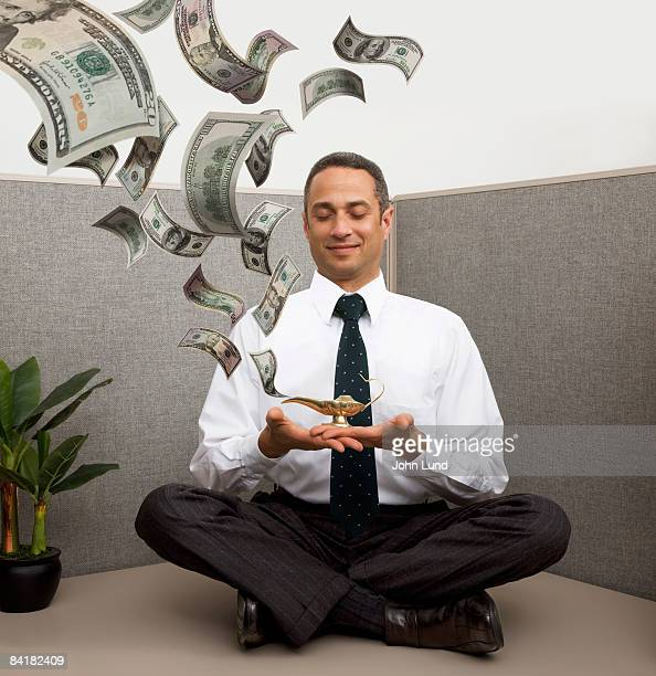 Business man with magic lantern spewing out money