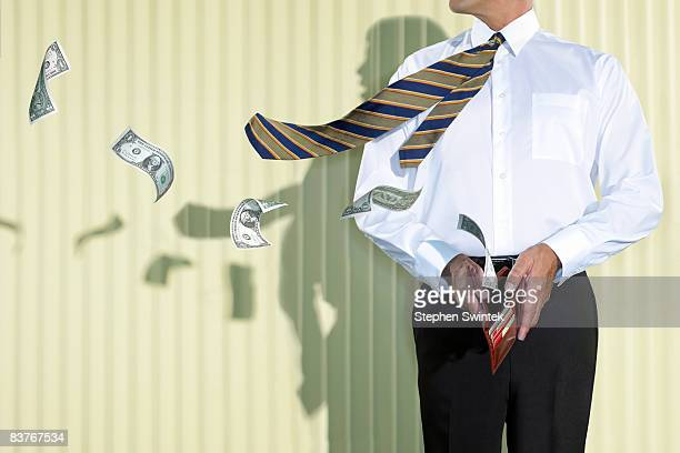 business man with money flying out of his wallet