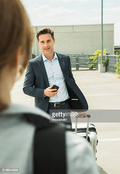 Business man with rolling suitcase and smartphone