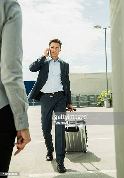 Business man with rolling suitcase telephoning with smartphone