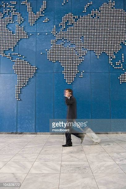 Business man with suitcase using mobile phone while walking past world map on wall
