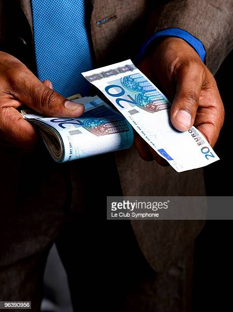 Business man with wad of euro bills