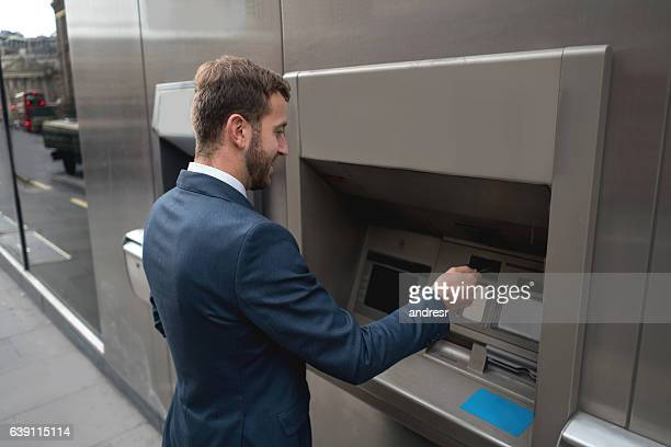 Business man withdrawing cash from an ATM