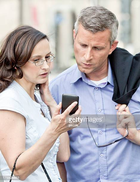 business man, woman looking concerned at mobile computer