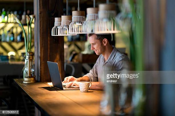 ビジネスの男性のカフェで働く