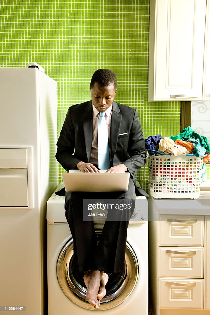 Business man working on laptop in the kitchen : Stock Photo