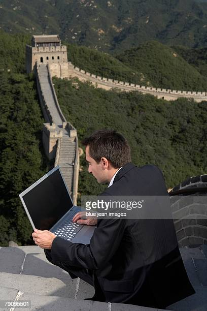 Business man working with a laptop on the Great Wall.