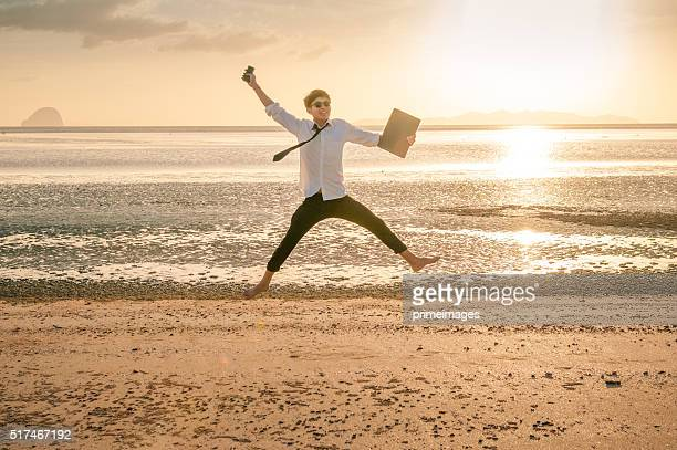 Business-Mann arbeitet mit Laptop und Smartphone am Strand im Hintergrund
