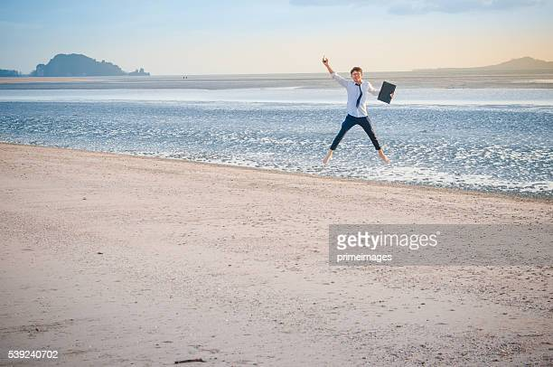 Business man working with laptop and smartphone beach background
