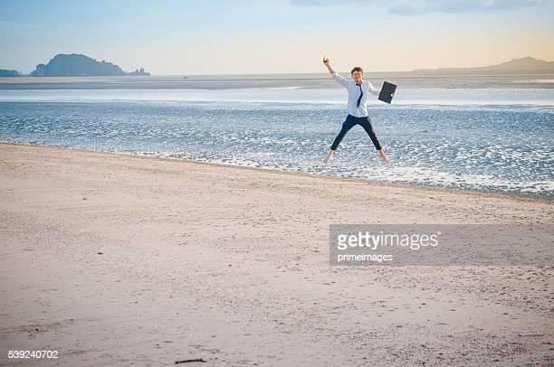 Homme d'affaires travaillant avec un ordinateur portable et un smartphone sur la plage en arrière-plan