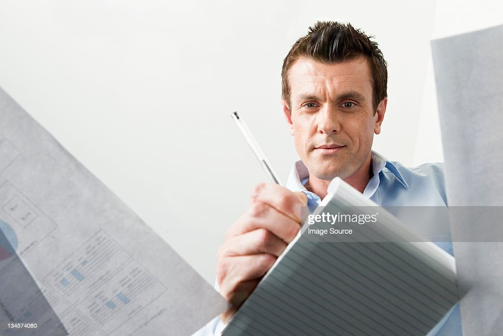 Business man writing in a notebook : Stock Photo