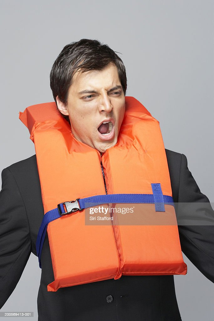 Business man yawning and wearing life jacket : Photo