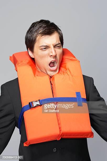 Business man yawning and wearing life jacket