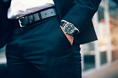 Close up of a business man's hand wearing a watch. Hand in pocket with wrist watch.