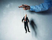 Businessman's hand controlling a worker marionette.
