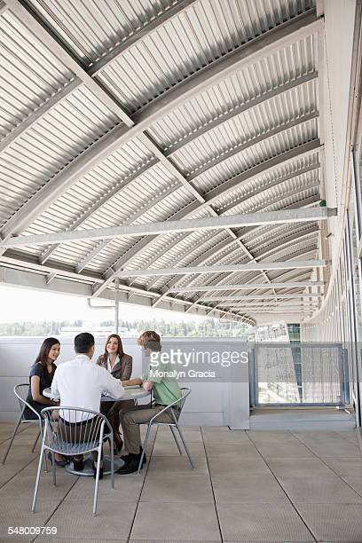 Business meeting at balcony table outside office building