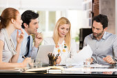 Young businesspeople in a meeting discussing about future strategies. Businessmen and businesswomen discussing the benefits of joint venture. Business teamwork working together in a modern office.