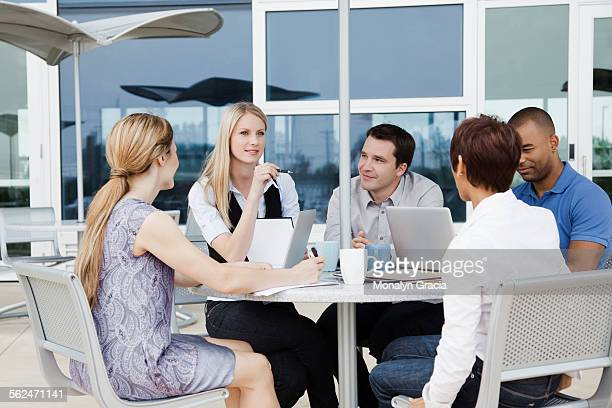Business meeting at patio table outside office building