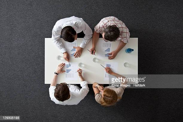A business meeting with three businessmen and a businesswoman, overhead view